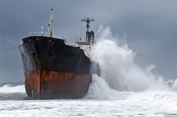 Waves crashing against a large ship.
