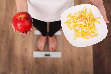 A young beautiful woman is on the scales and make a choice between an apple and potato chips. The concept of healthy eating. Healthy Lifestyle. Diet.