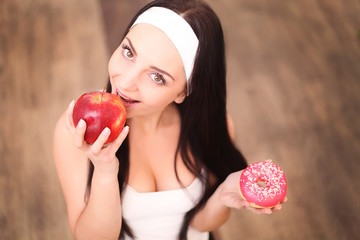 Beautiful young woman making choice between apple and donut, close up