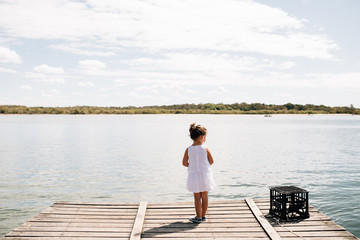 Rear view of girl standing on jetty