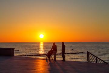 Familie mit Kind, Silhouette in der aufgehenden Sonne