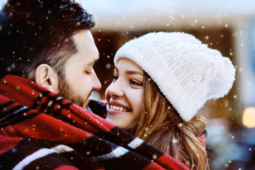 Outdoor close up portrait of young beautiful happy smiling couple. Models looking at each other, bundled up in tartan blanket. Christmas, new year, winter holidays, dating concept. Day light, snowfall
