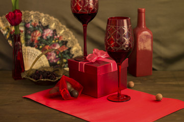Red gift box with two glasses of wine staged still-life image