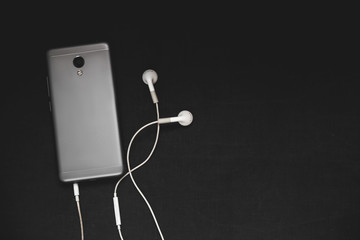 Smartphone with headphones on a black background