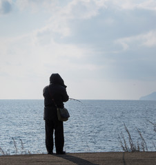 Man cast fishing from the shore into the blue gray waters of Lake Baikal. He is dressed warmly all in black with his back to the camera.