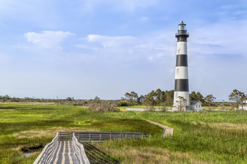 A board walk leads the eye to the historic Bodie Island Lighthouse at Cape Hatteras National Seashore on the Outer Banks of North Carolina.