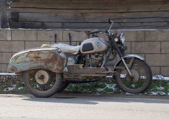 Vintage motorcycle with rear platform and two rear wheels parked in front of block wall. The motorcycle is rusted and in disrepair.