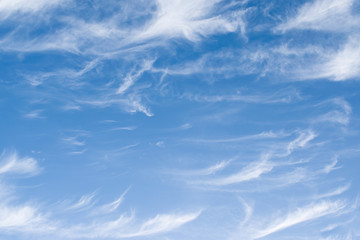 White clouds of unusual shape on a blue sky in winter
