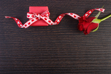 Wrapped gift with red ribbon and rose for Valentines Day, copy space for text