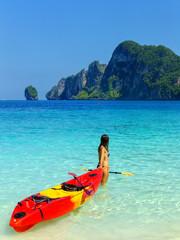 Young woman standing with kayak at Ao Yongkasem beach on Phi Phi