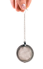 tea strainer on a chain in  hand isolated  white background