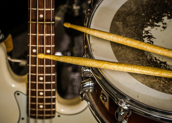 snare drum with drumsticks and bass guitar