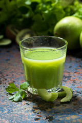 glass of juice of celery and greens on blue background, vertical