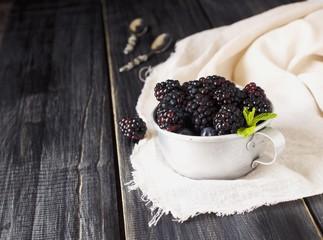 fresh raw blackberries in metal cup, selective focus