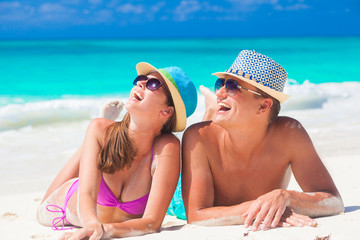 couple enjoying their time lying on sand at tropical beach