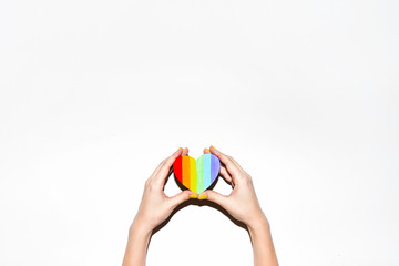 Rainbow gay pride symbol heart shaped in hands on white