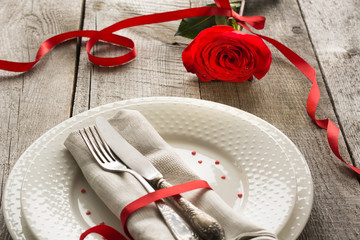 Romantic dinner concept. Festive table setting for Valentines Day on wooden background. Red rose with ribbon on plate.