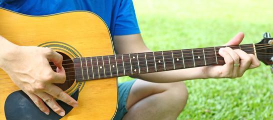 Man playing guitar on green grass