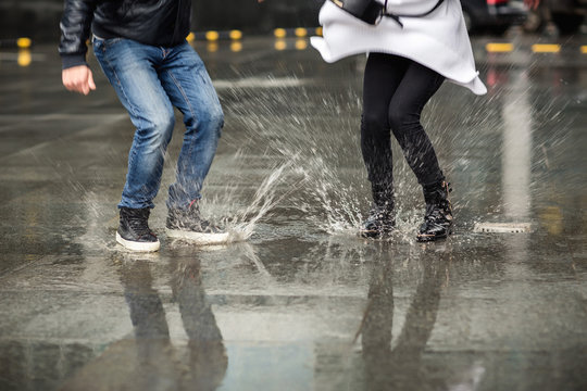 Wet shoes of couple, man and woman jumping in puddle