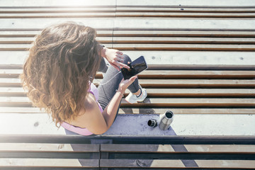 Summer sunny day. Top view,young woman in sportswear sits outside on concrete steps, using smartphone, listening to music on headphones. Nearby stands a metal water bottle.Woman resting after workout.