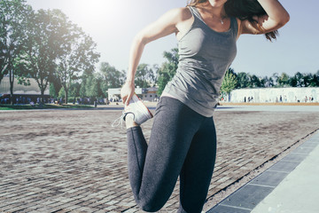 Cropped image. Summer sunny day. Young woman in gray sportswear standing outdoors and stretch before exercise. Girl stretches legs before jogging.