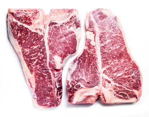 Raw T-bone steaks on the white background.