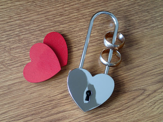Wedding rings in the lock and two red hearts