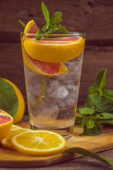 Fresh lemonade in a glass beaker with ice, green mint, red orang