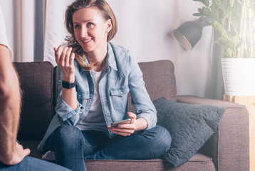 Front view of a young smiling woman in a denim jacket sitting on the couch in the room and talking to a man sitting in front of her. A girl holding a smartphone. Teamwork, discussion a business plan.