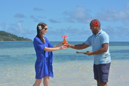 Fijian man serve a tropical cocktail drink to a tourist woman in