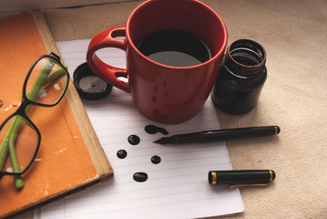 Ink, pen, notebook and coffee