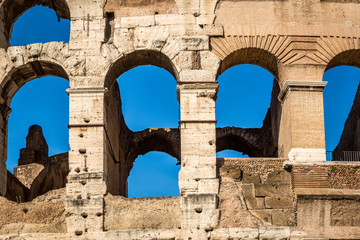 Detail of exterior arched openings / windows at the colosseum in Rome Italy, blue sky background.
