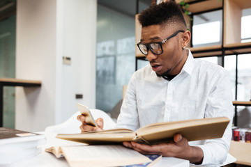 Confused african student in library learning education material