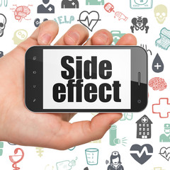 Health concept: Hand Holding Smartphone with Side Effect on display