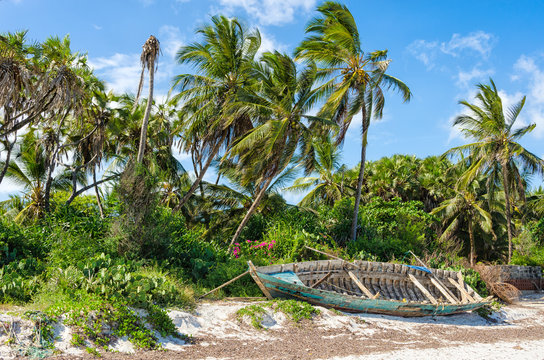 Abandoned shipwreck stranded on a sandy beach under palm trees and deep blue sky on a