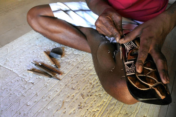 Hands of Indigenous Fijian man wood carving a sea turtle