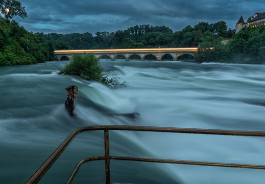 Long night exposure of the Rhine River right before the Rhine Falls. A train leaves its light trails behind on the bridge in the back. A railing is in the foreground on the waters edge.