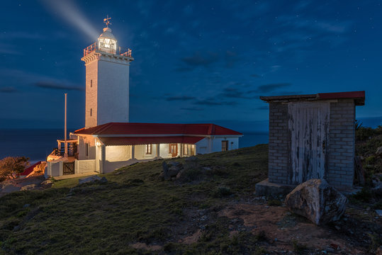 Lighthouse with rotating beacon and its light beam under blue cloudy night sky full of stars also showing a little shabby shed in the foreground