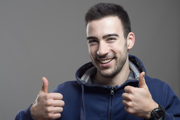 Excited cheerful young man wearing hoodie showing thumbs up gesture