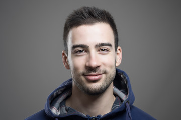 Horizontal portrait of positive friendly young happy man smiling at camera