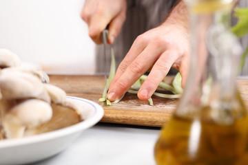 Kucharz sieka warzywa na desce do krojenia.