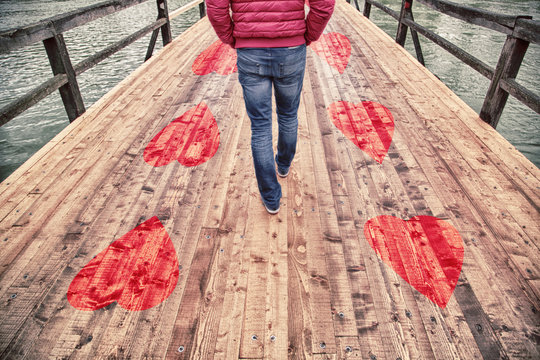 Happy man in love walking alone on a wooden bridge floor with his hands in his pockets.