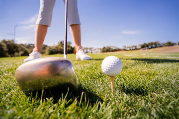 Close up shot of a golf ball and driver on green fairway grass. Feet of female golf player on course. Beautiful sunny Landscape, green hills, blue sky. Portugal.