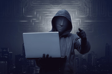 Hacker man with mask holding laptop while appoint