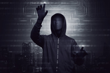 Hooded hacker with mask using virtual screen to hacking system security