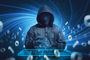 Hooded hacker with mask typing on virtual keyboard
