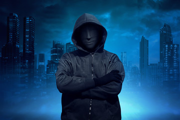 Hooded man with anonymous mask standing