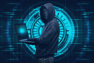 Hooded hacker with mask typing on laptop
