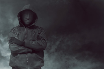 Hooded man with mask standing alone