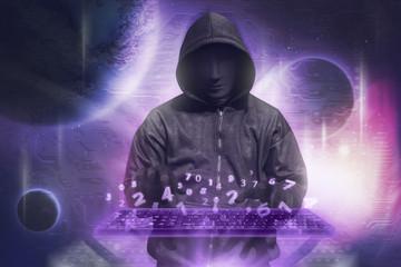 Hacker in mask typing keyboard hacking binary data